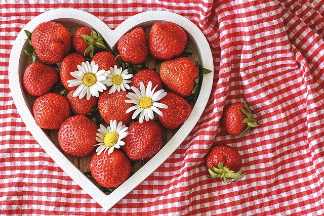 heart shaped dish of strawberries on a red and white checked tablecloth